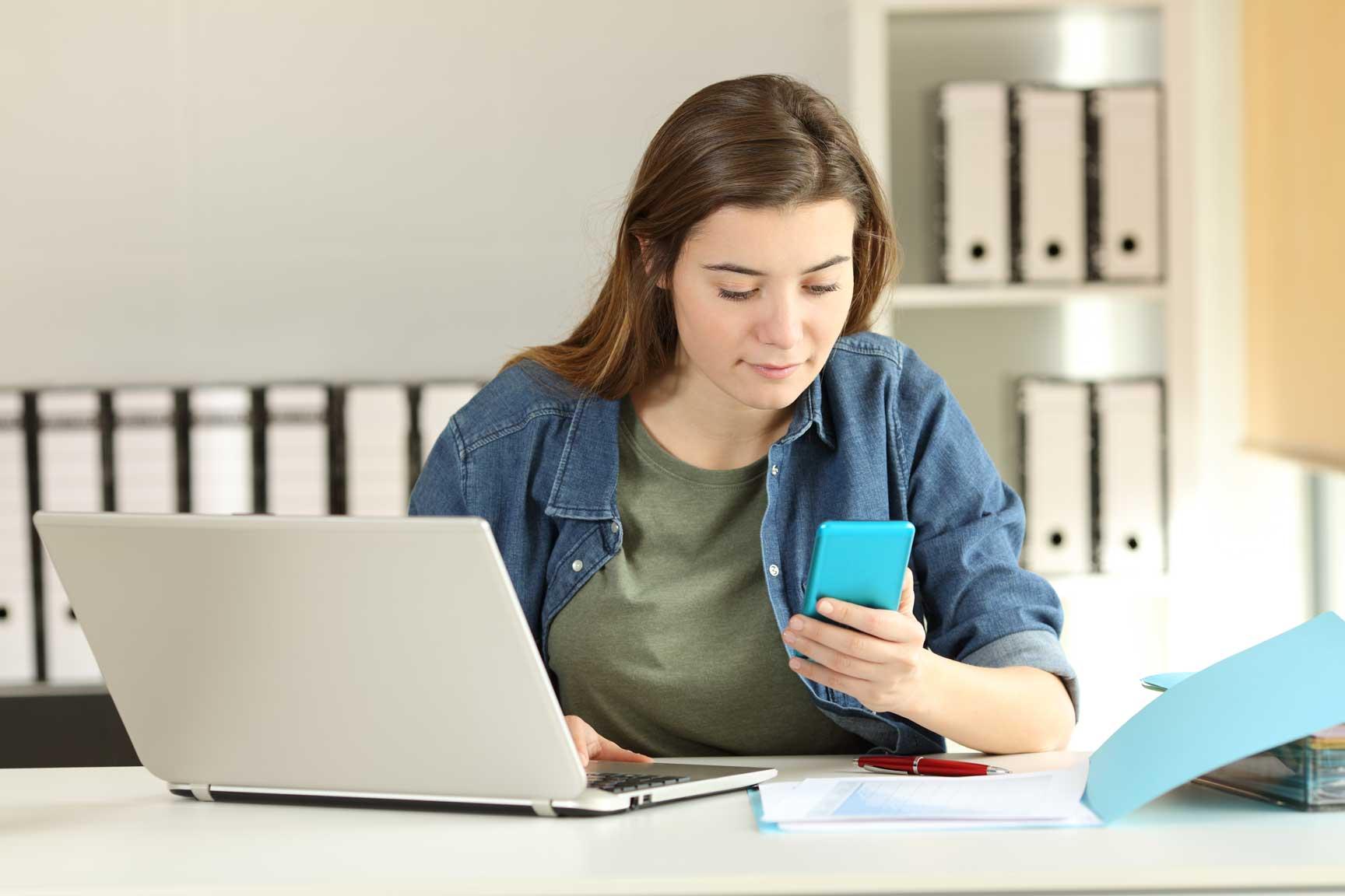 Junge Studentin schaut auf ihr Smartphone während sie lernt.