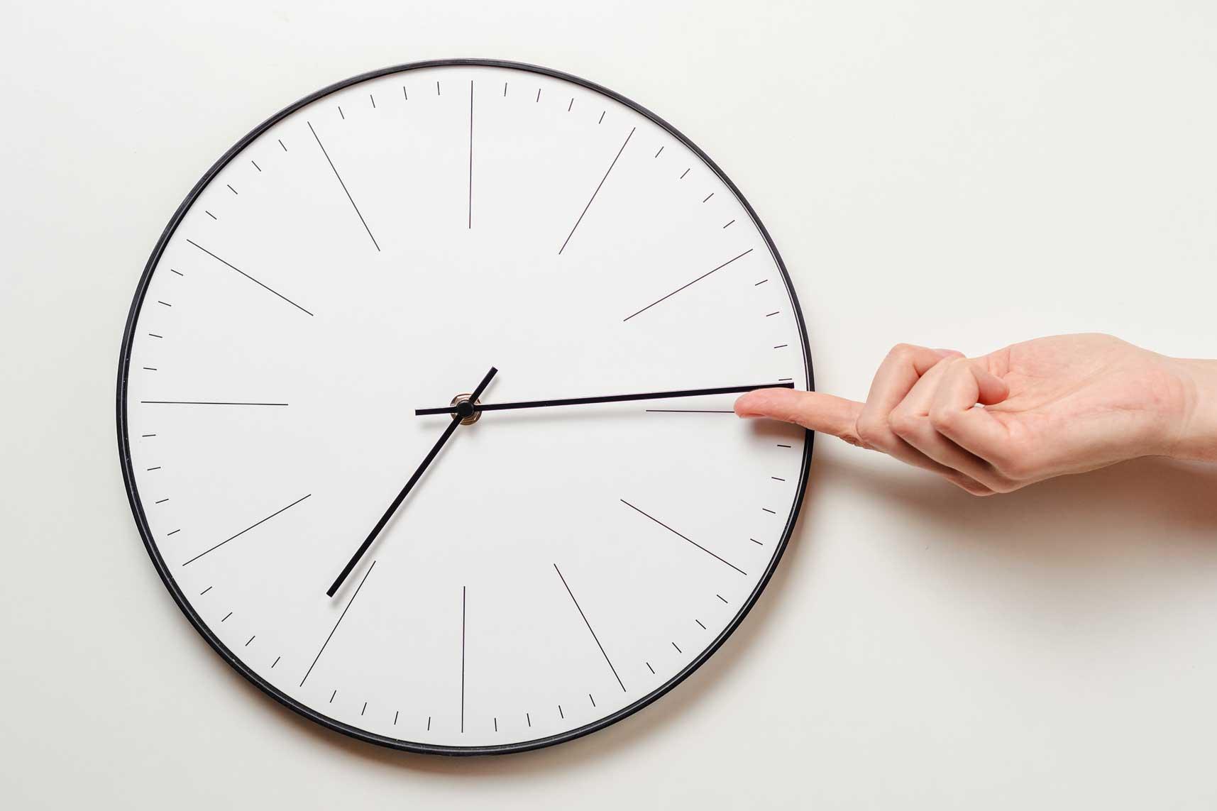 Nahaufnahme einer Wanduhr. Eine Hand ragt von links ins Bild und hält den Minutenzeiger fest.