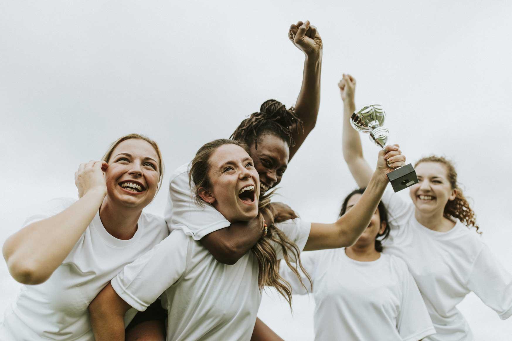 Vier junge Frauen feiern ihren Sieg, eine von ihnen hält einen Pokal in der Hand.