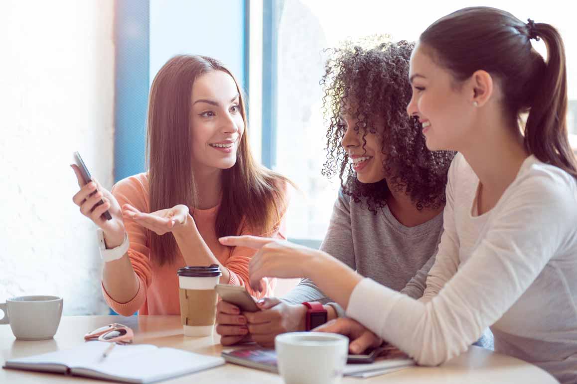 Drei Freundinnen sitzen gemeinsam im Café und zeigen sich gegenseitig etwas auf ihrem Smartphone.