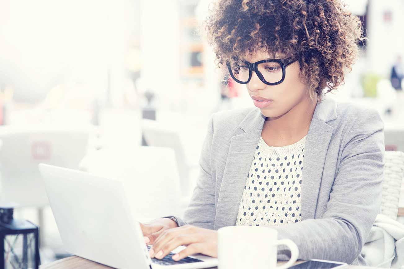 Eine junge Bewerberin checkt ihre Social Media Kanäle auf ihrem Laptop.