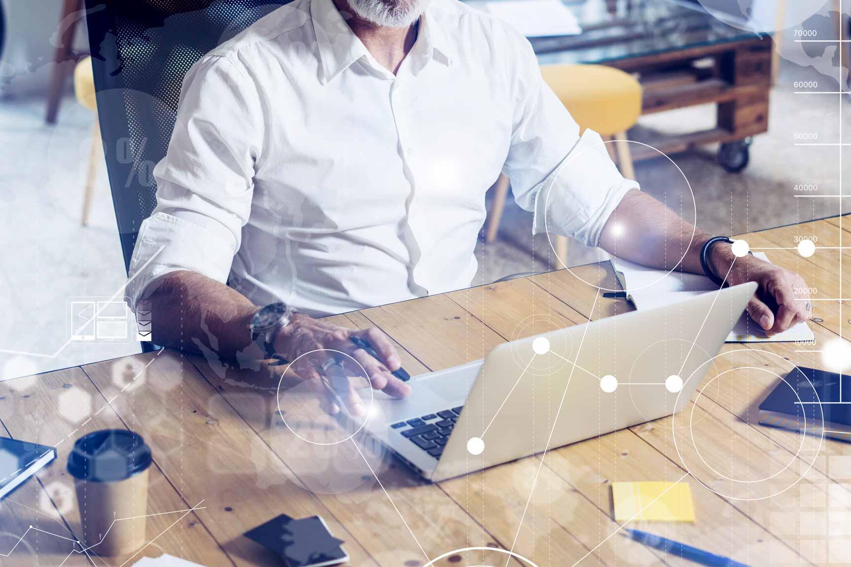 Eine erfahrener Mitarbeiter an seinem modernen Arbeitsplatz in einer vernetzten Welt.