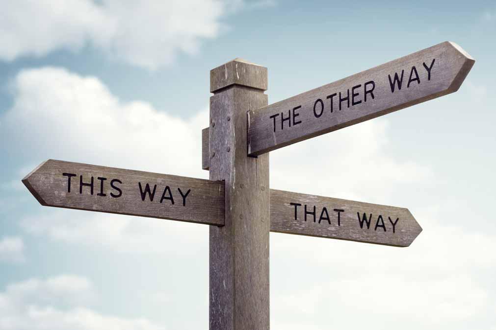 """Ein Straßenschild zeigt in verschiedene Richtungen. Auf den Richtungspfeilen steht: """"THIS WAY"""", """"THAT WAY"""" und """"THE OTHER WAY"""""""
