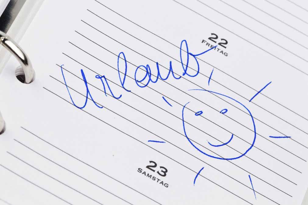 """Urlaubseintrag in einem Taschenkalender. Der Eintrag ziert das handgeschriebene Wort """"Urlaub"""", darunter ist eine Sonne gezeichnet."""