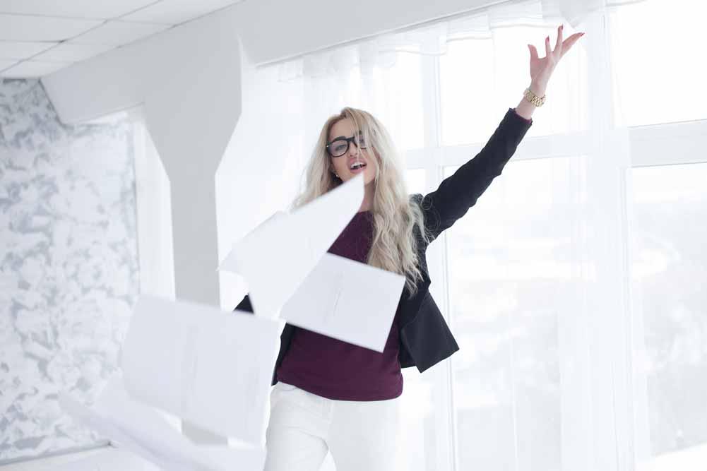 Eine Mitarbeiterin wirft einen Stapel Papier in die Luft.