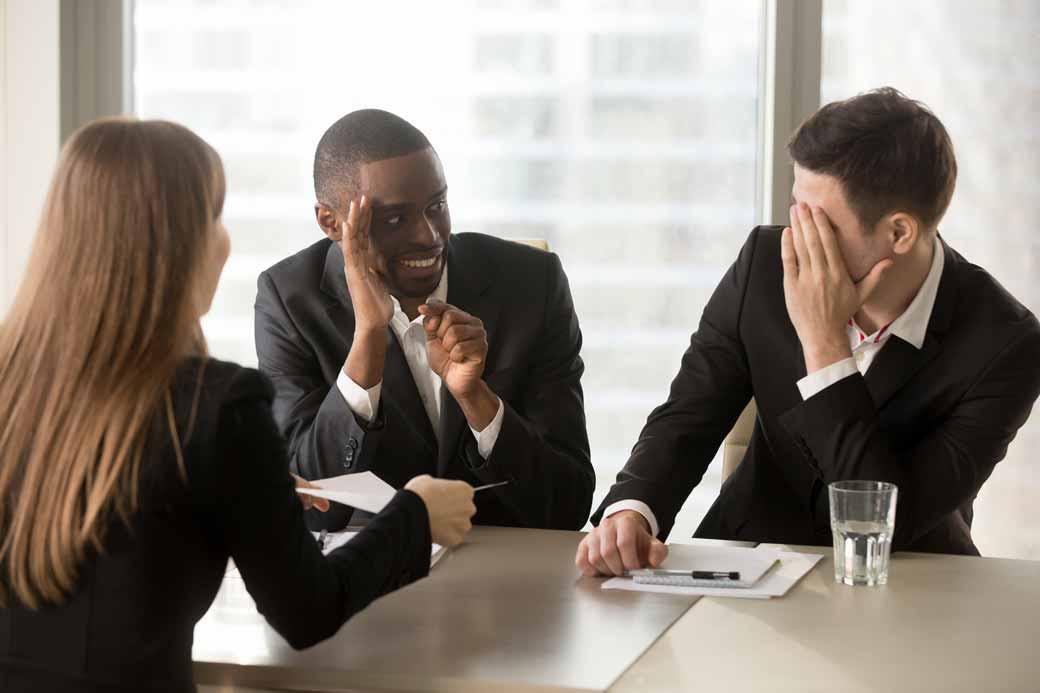 Zwei Mitarbeiter unterhalten sich belustigt über eine Kollegin.