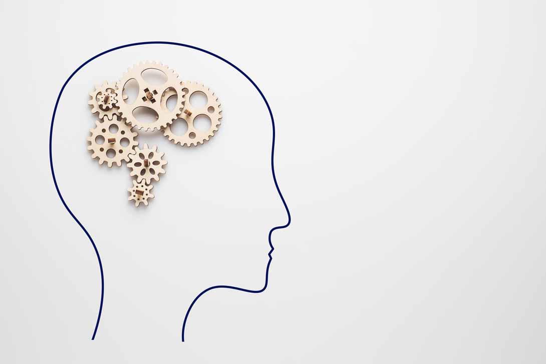 Zahnräder als bildliche Metapher für das menschliche Gehirn und eine Silhouette von einem Kopf darum gezeichnet.