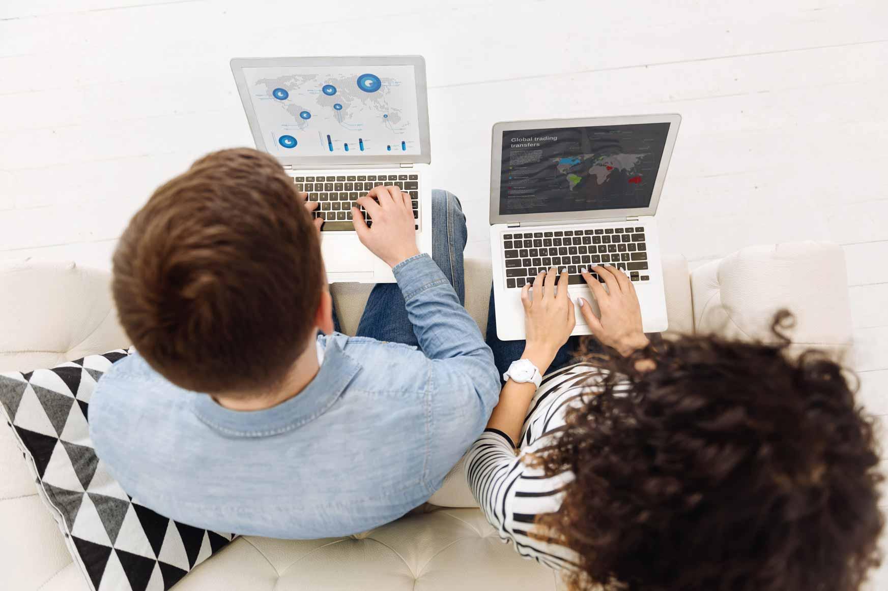 Zwei junge Mitarbeiter der Generation Y am Laptop.
