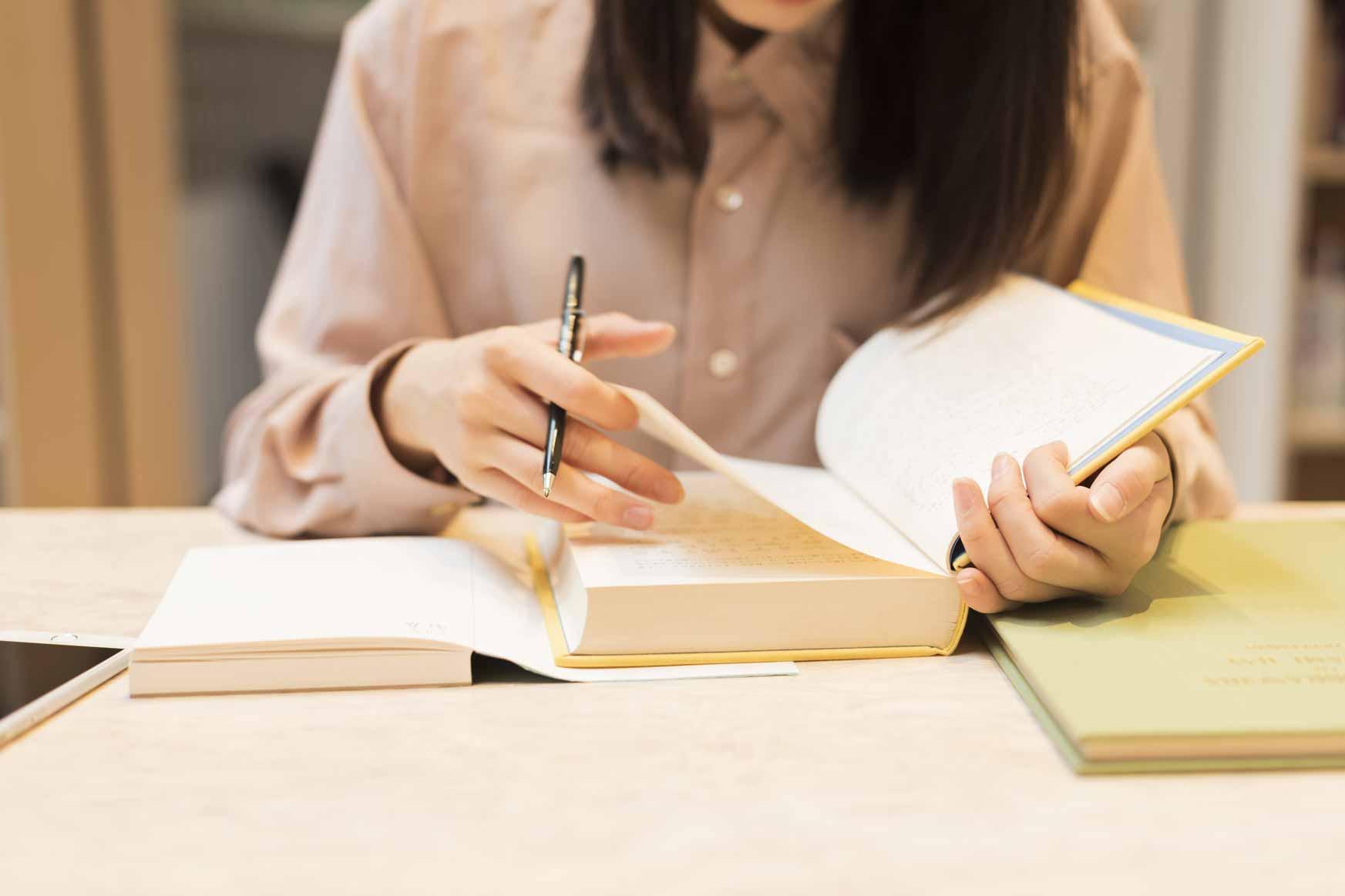 Eine junge Studentin sitzt am Tisch und schaut in ein buch. In der Hand hält sie einen Stift.