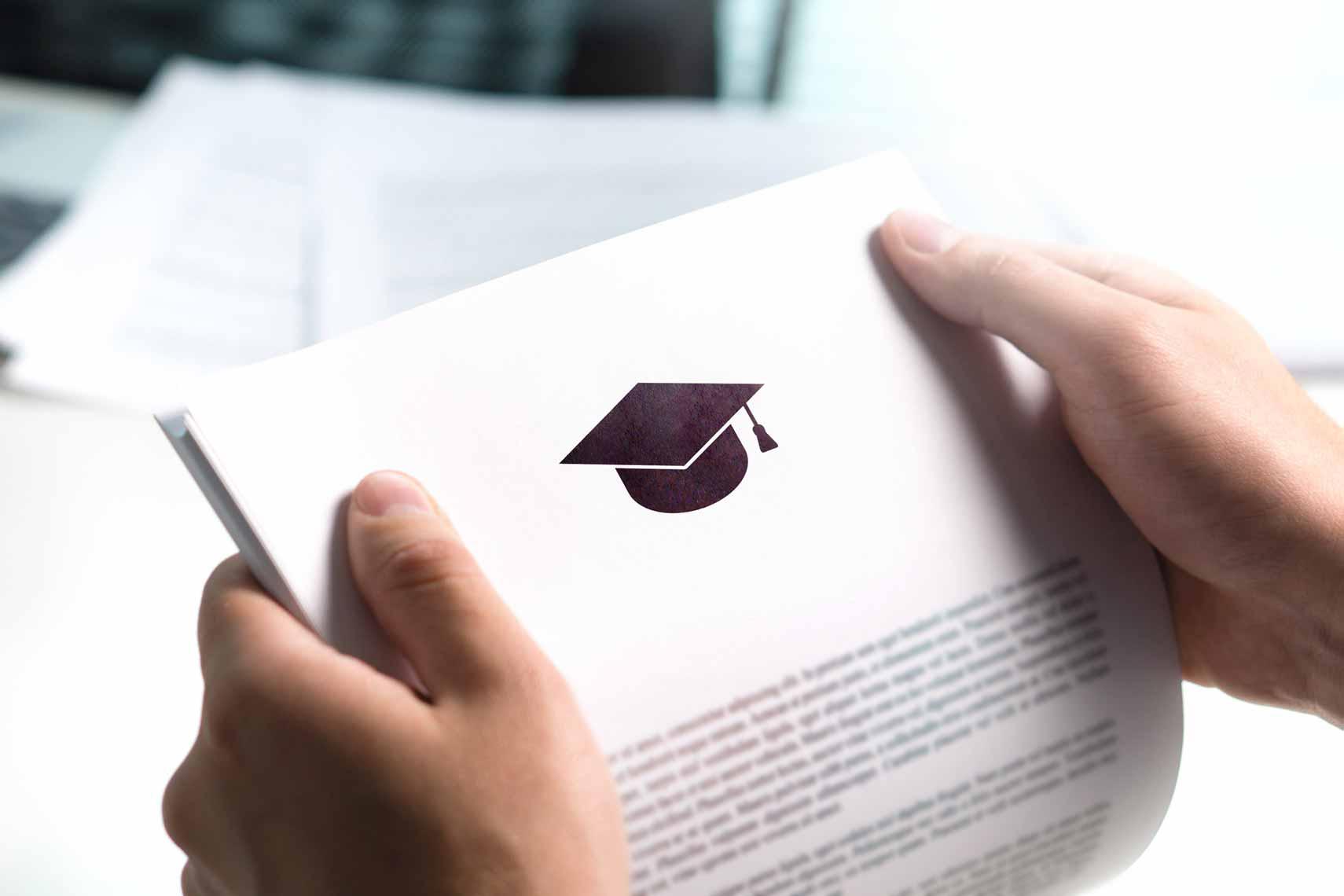 Zwei Hände halten ein Dokument auf dem ein Doktorhut gedruckt ist.
