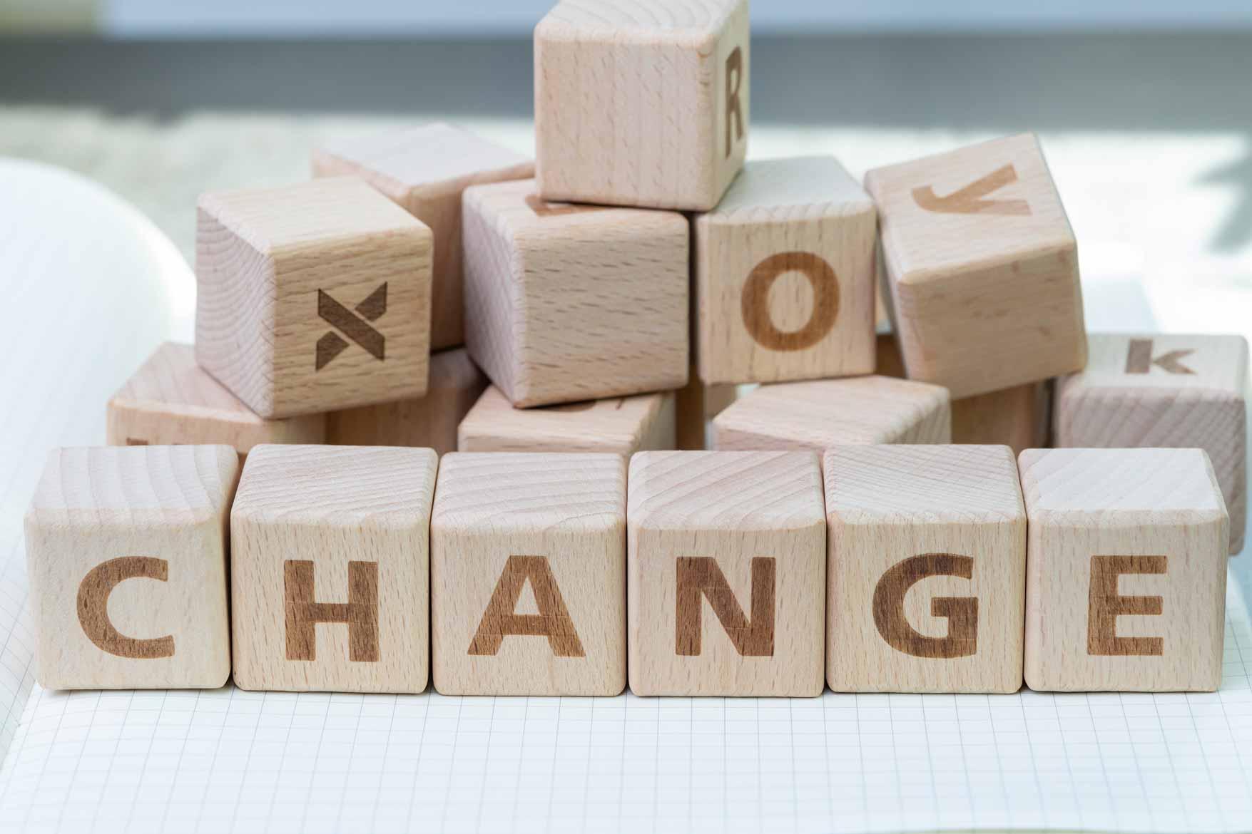 """Holzwürfel gestappelt auf einem Collegeblock. """"Change"""" steht in der vordersten Reihe auf den Würfeln geschrieben."""