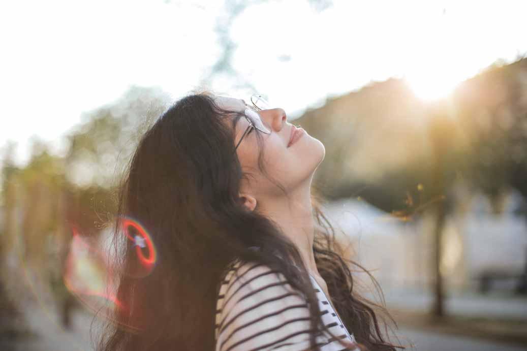 Junge Studentin schaut als Teil einer Achtsamkeitsübung mit geschlossenen Augen, zufrieden in den Himmel.