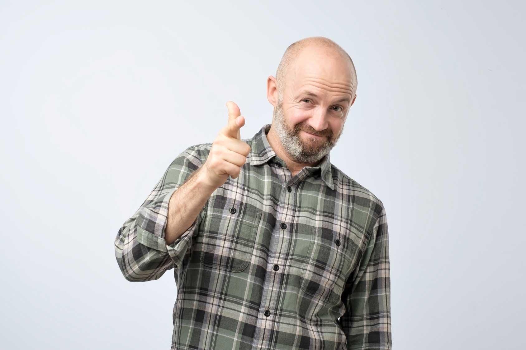 Ein Mann mit Glatze und Bart zeigt bestätigende Gesten in Richtung Betrachter.