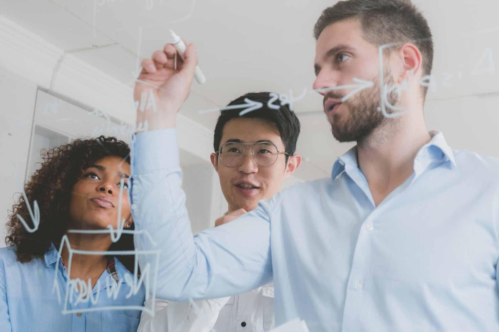Ein Experte aus dem Fachbereich zeichnet auf eine Tafel und erklärt dabei den Bewerbern ihre zukünftige Jobrolle.