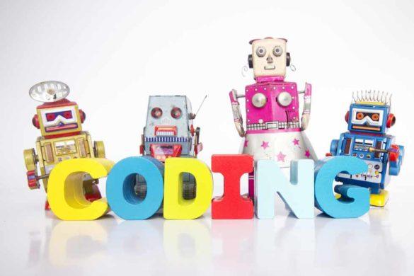 """Vier Roboter vor einem """"Coding"""" -Schriftzug."""
