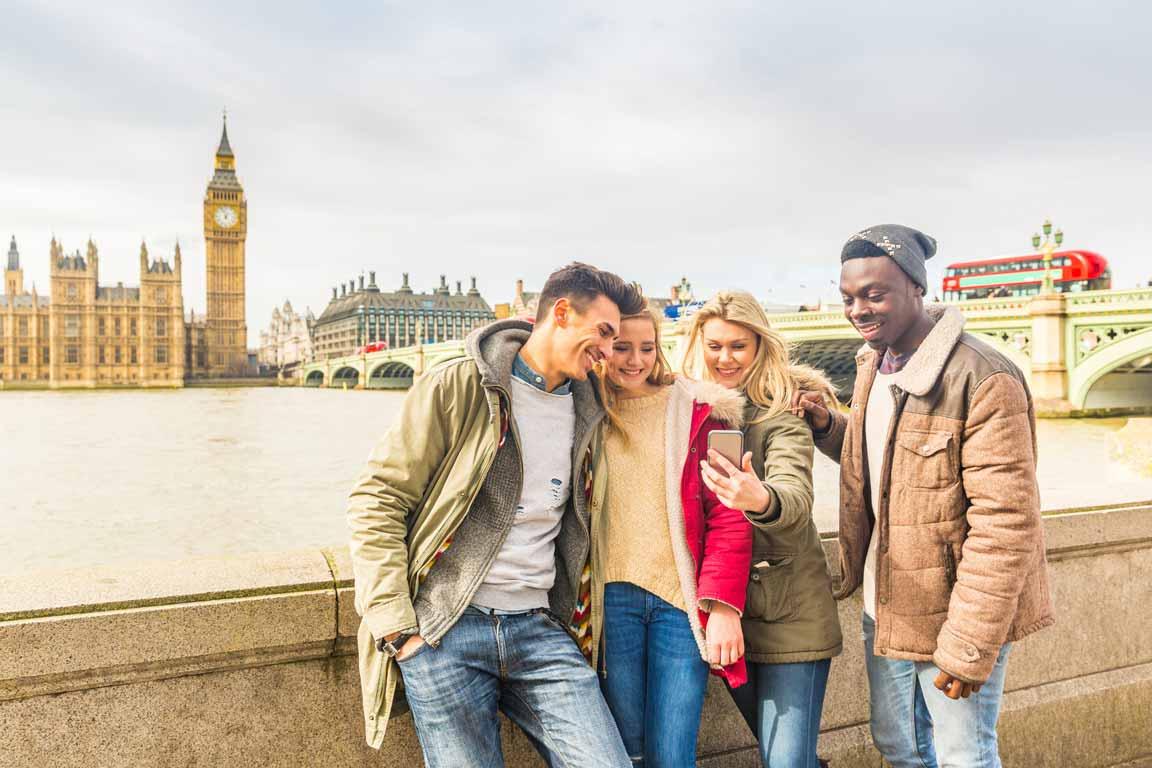 Eine Gruppe junger Menschen am Ufer der Themse in London schaut gemeinsam auf ein Smartphone.
