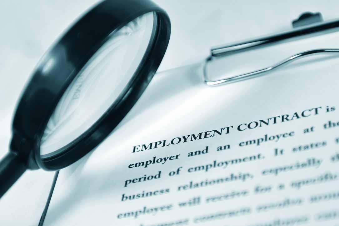 Eine Lupe ist auf einen Arbeitsvertrag gerichtet.