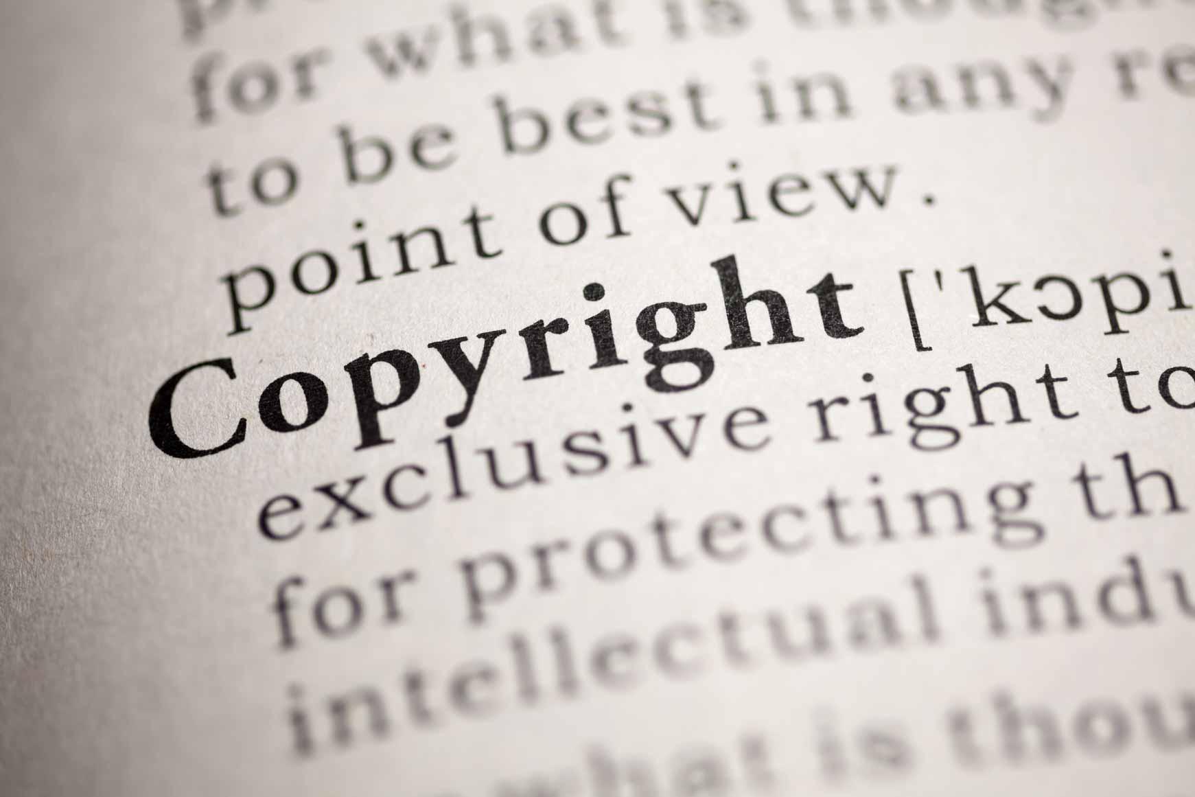 """Eine Textseite in einem aufgeschlagenen Buch. Im Zentrum steht die Aufschrift """"Copyright""""."""