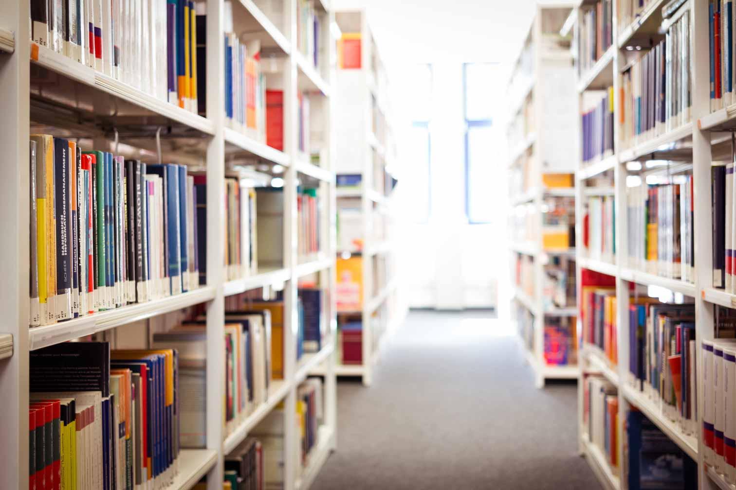 Ein Flur zwischen Bücherregalen in einer Bibliothek.