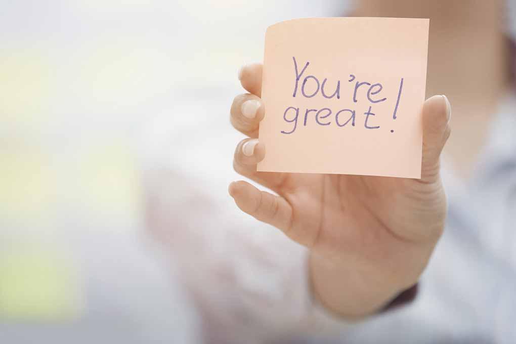 """Ein Post-it mit der Aufschrift """"You're great!"""" wird ins Bild gehalten."""