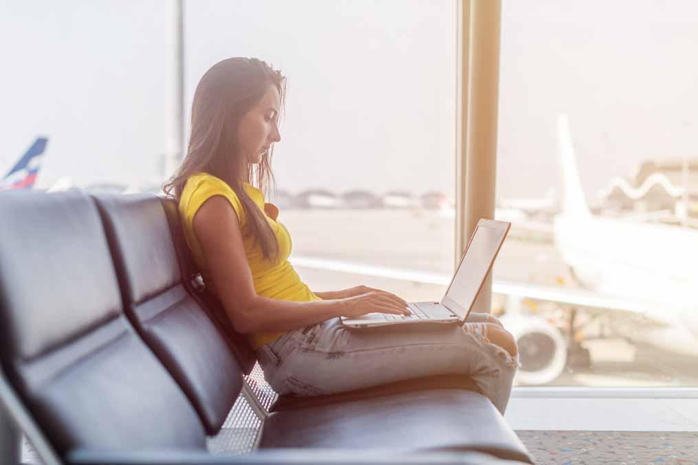 Studentin mit Laptop am Flughafen.