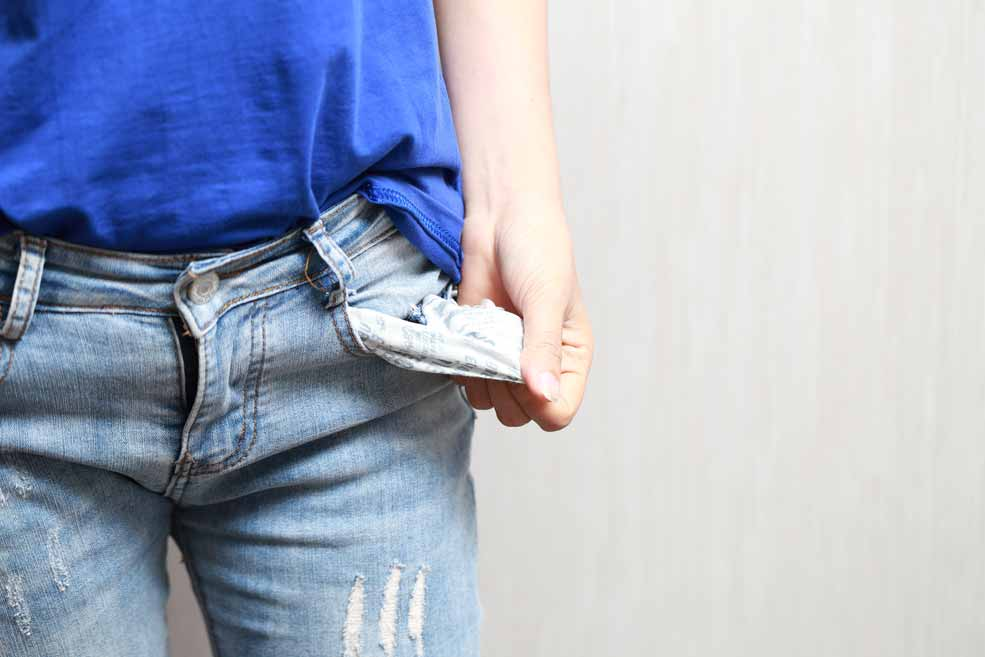 Eine Absolventin zeigt ihre leeren Taschen.