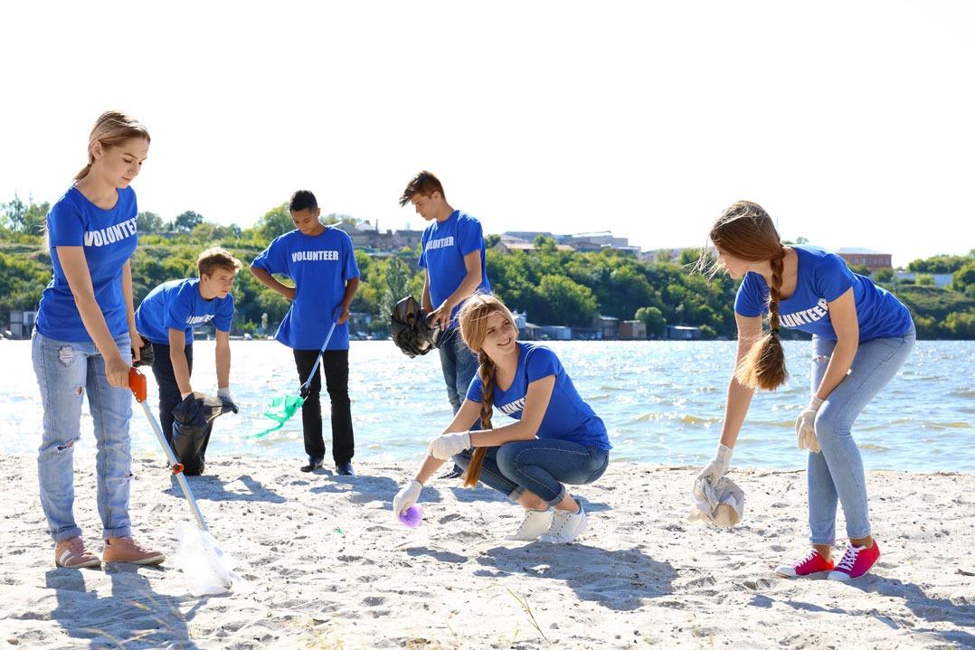 6 junge Volunteers sammeln am Strand Müll auf