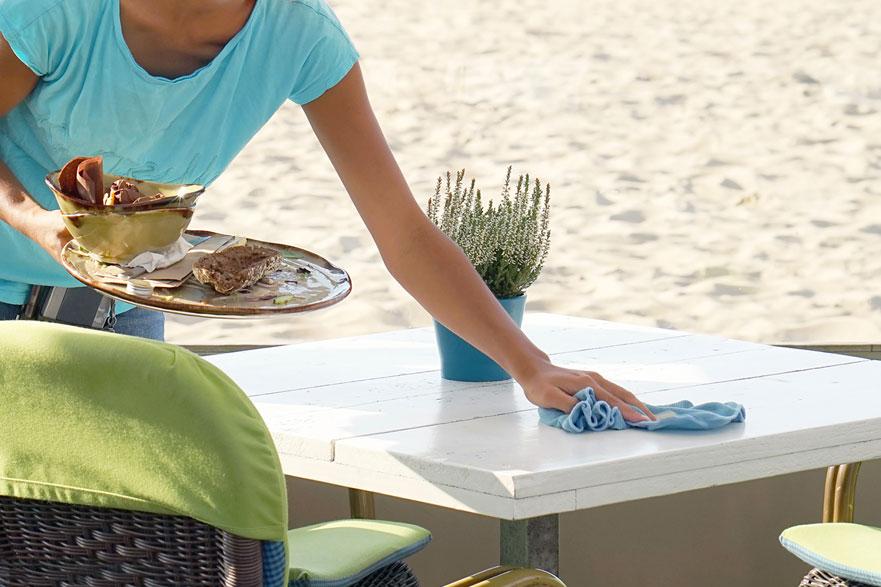 Junge Kellnerin wischt an der Strandbar einen Tisch mit einem Lappen ab und hat ein Tablett in der anderen Hand