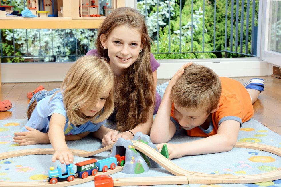 Au Pair Mädchen spielt mit 2 kleinen Kindern Eisenbahn