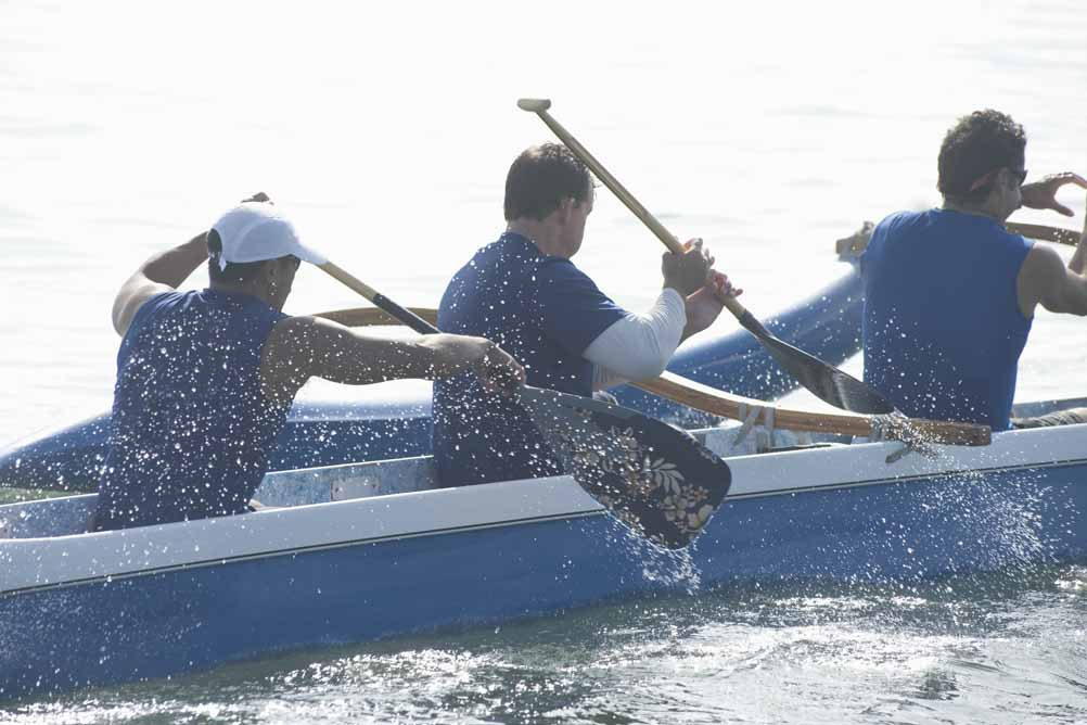 Drei Männer bei einem Kanurennen auf einem Fluss.