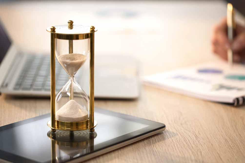 Eine Sanduhr steht auf einem auf einem Tablet auf einem Schreibtisch im Büro.