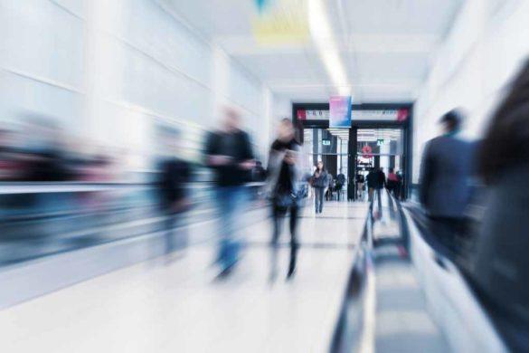 Mehrere Menschen laufen hastig durch einen Durchgang am Flughafen.