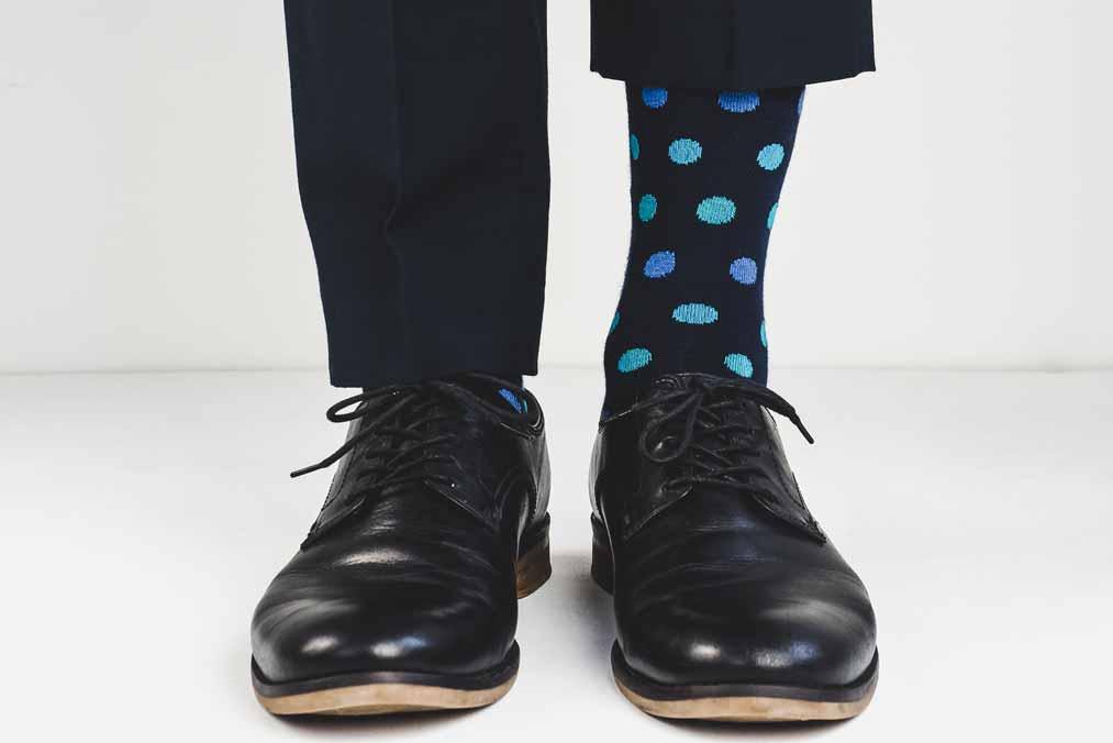 Schwarze Männerschuhe aus Leder und bunte Socken.