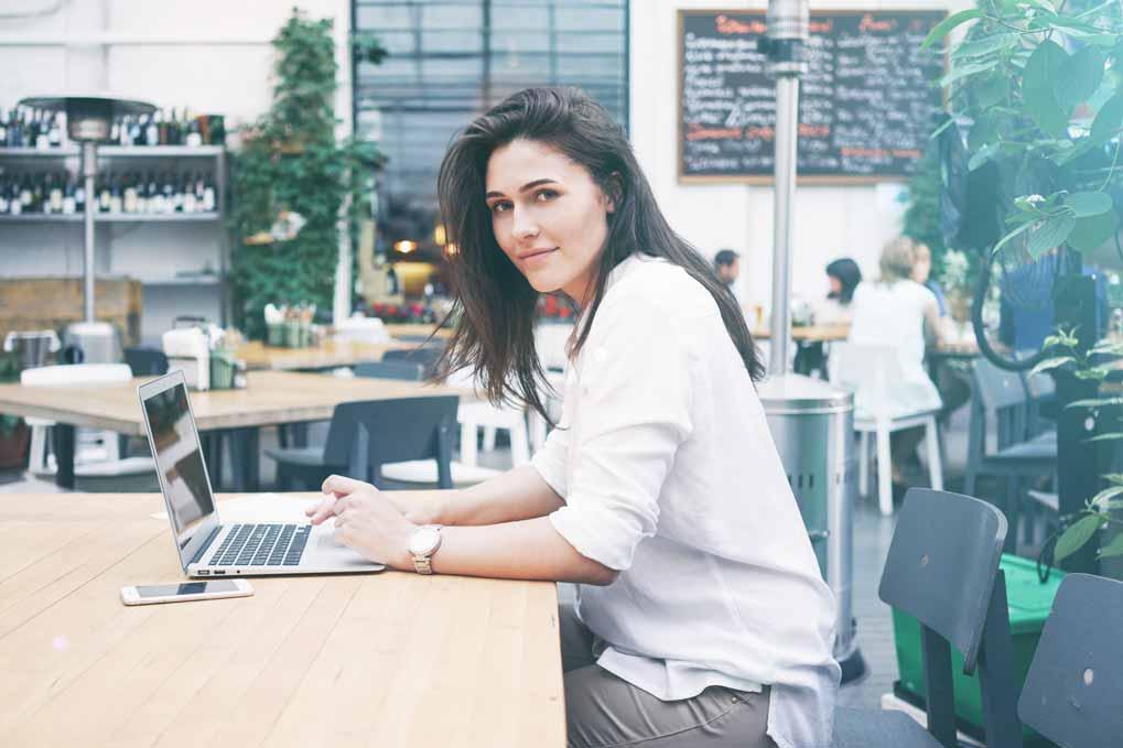 Geschäftsfrau arbeitet unterwegs in einem Cafe.