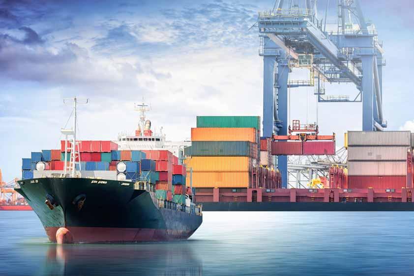 Ein Containerschiff legt ab im Hintergrund ein Containerumschlagplatz.