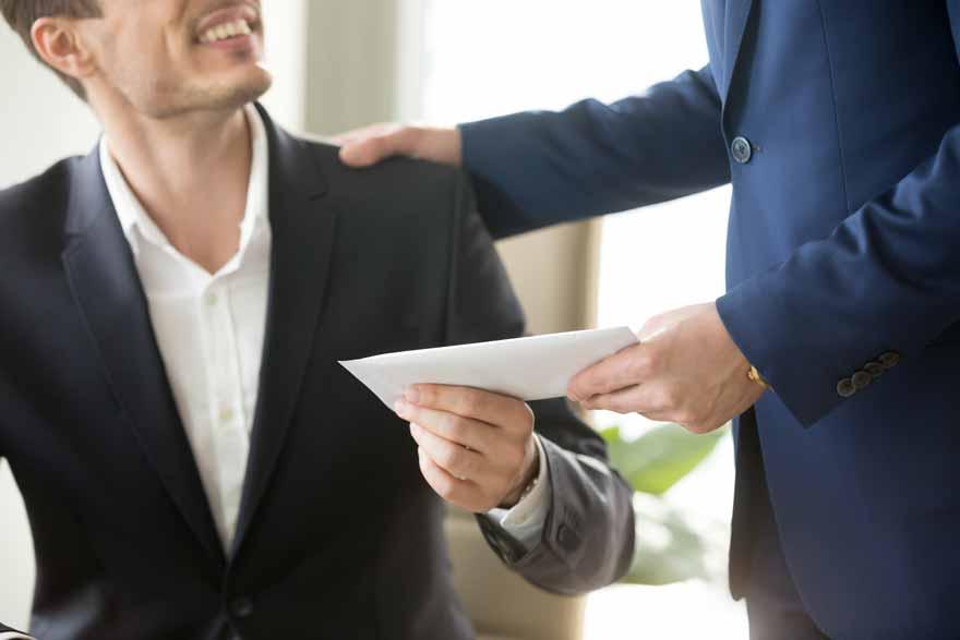 Der Chef übergibt einen weißen Umschlag an einen Mitarbeiter
