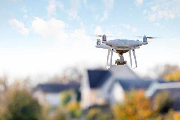 Internet of Things – Drone fliegt über einem Wohngebiet in den Sonnenuntergang.
