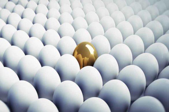 Ein goldenes, glänzendes Ei in mitten normaler weißer Eier.