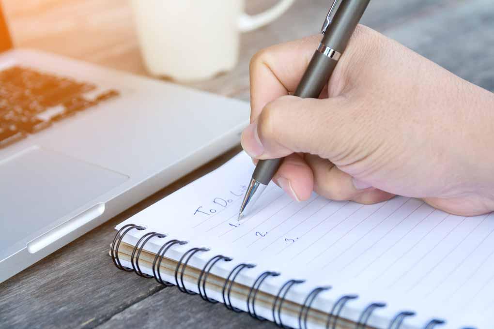 Eine Hand die eine ToDo-Liste auf einem Block schreibt.