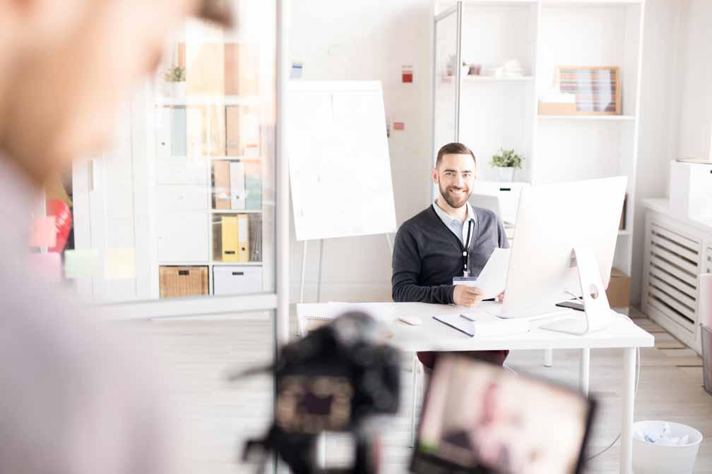 Glücklicher Mitarbeiter an seinem Arbeitsplatz wird gefilmt.
