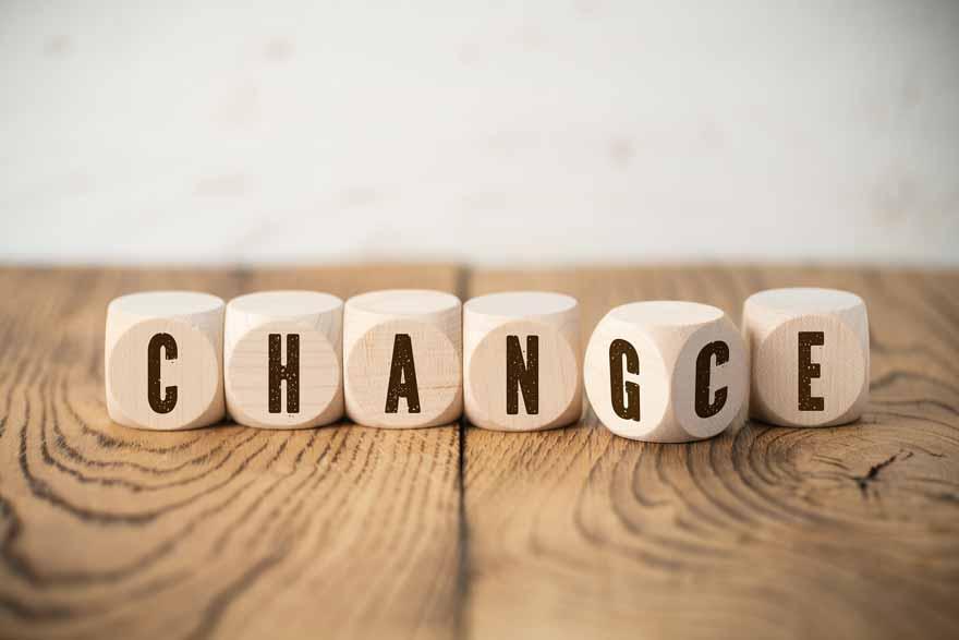 Holzwürfel auf denen Change bzw. Chance geschrieben steht, liegen auf einem Holztisch