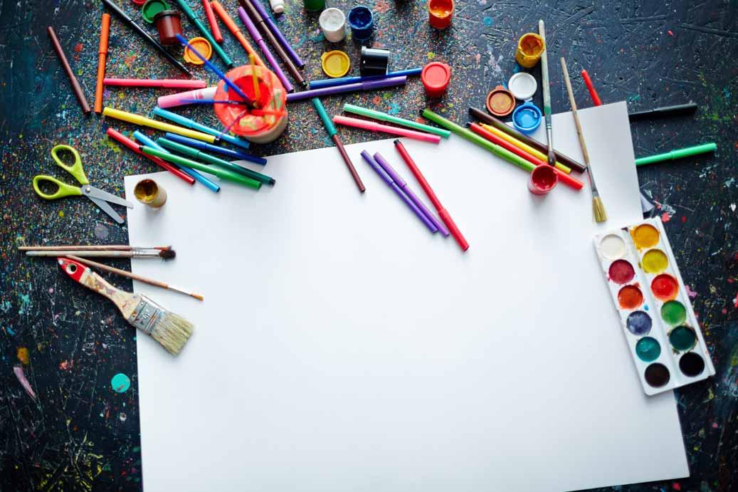 Kreativer Arbeitstisch mit bunten Farben, Pinseln und einer weißen Leinwand.