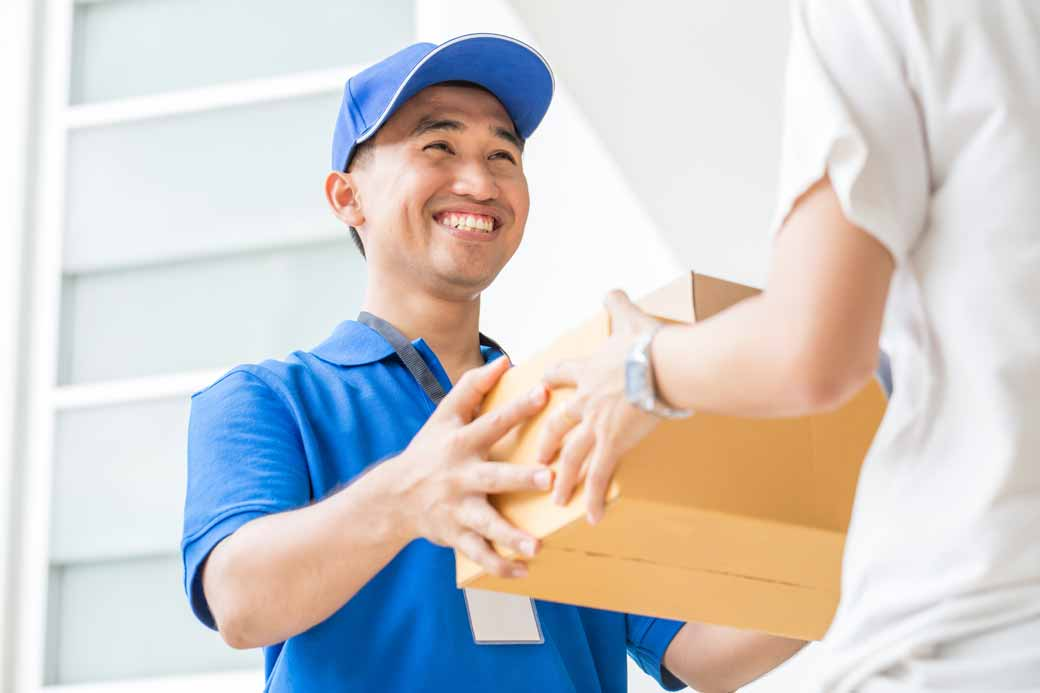 Ein Paketbote übergibt ein Paket an eine Person.