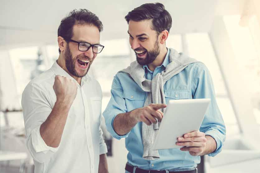 Mitarbeiter mit Tablets freuen sich über die Vorteile der Blockchain.