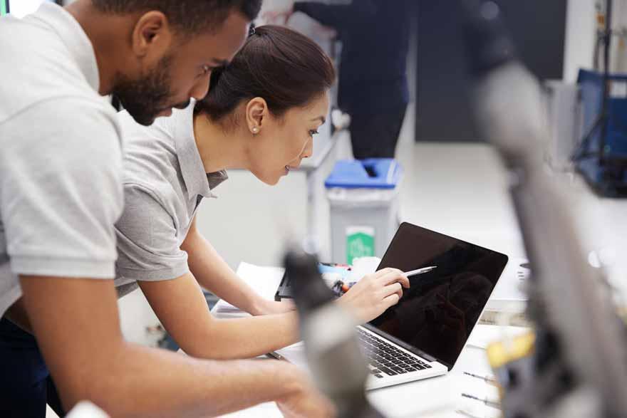 Eine Mitarbeiterin zeigt ihrem netten Kollegen etwas auf einem Laptop.