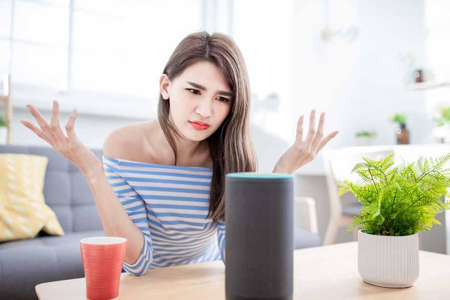 Eine ratlose Frau vor einem Smartspeaker.