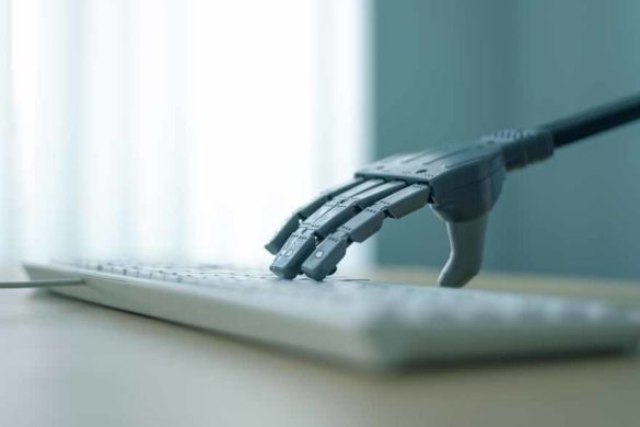 Eine Roboterhand tippt auf einer Computertastatur