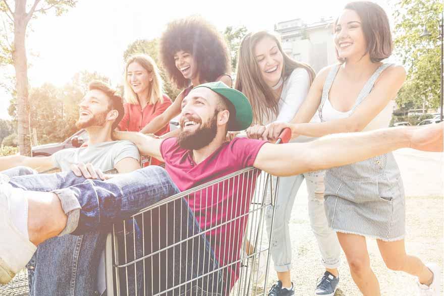 Studenten schieben sich gegenseitig im Einkaufswagen umher.