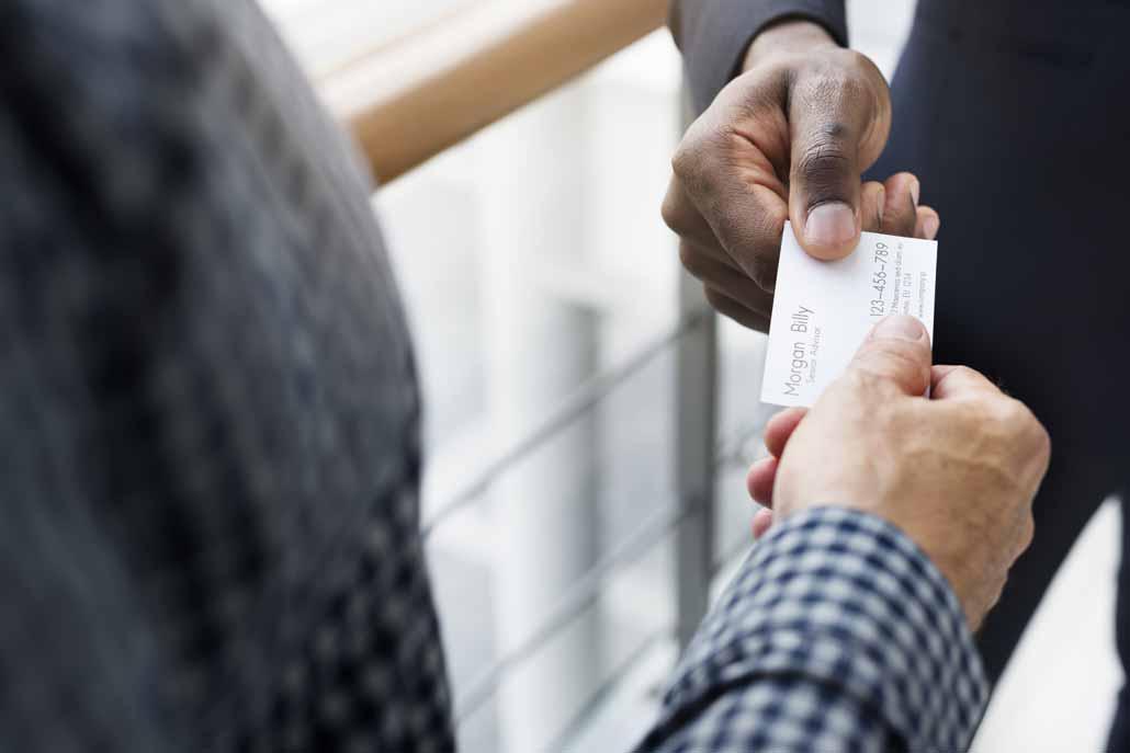 Übergabe einer Visitenkarte bei einem Businessmeeting.