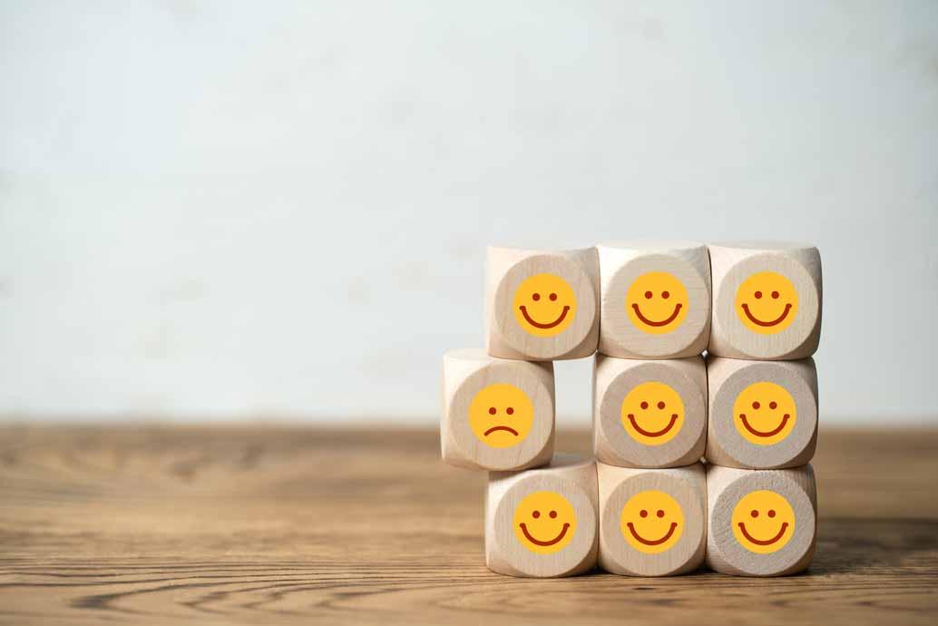 Würfel mit lächelnden Smileys und einer der unzufrieden ist.